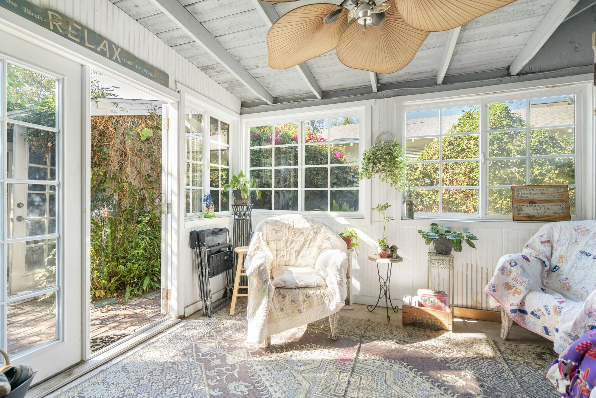 View of step-down sun room entered via the kitchen, with double pane windows and French doors leading to the back yard.