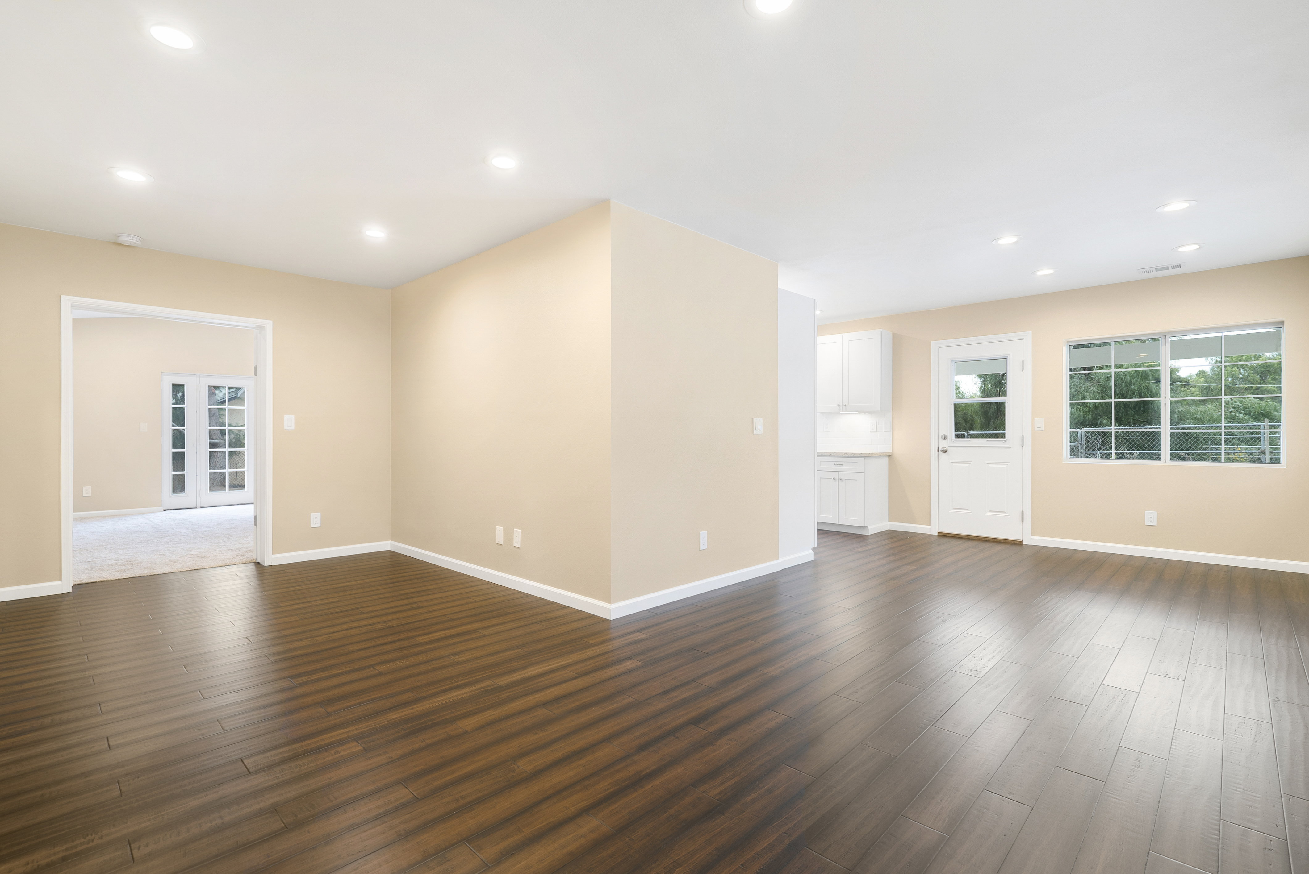 View from corner of living room with view of double door entry to master suite on the left, and the dining room and kitchen to the right. All new wood flooring, paint, doors, and recessed lighting.