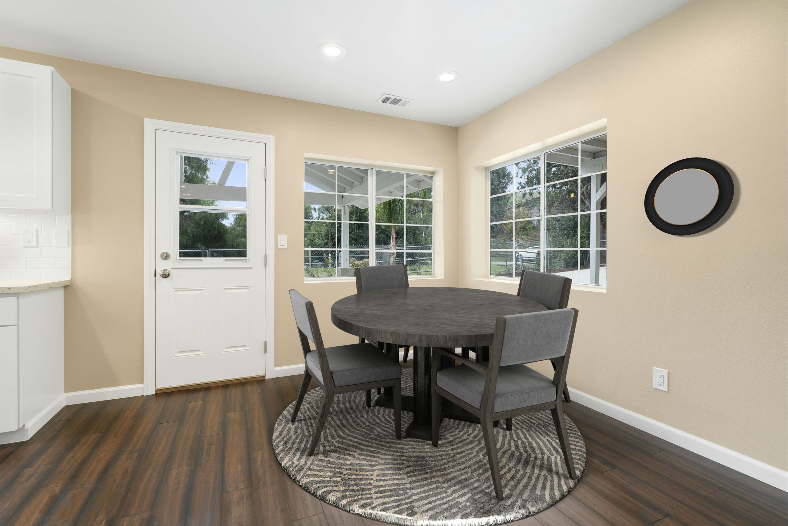 Dining area adjacent to kitchen, with brand new flooring, brand new recessed lighting, brand new door, and double pane windows. This photo is virtually staged.