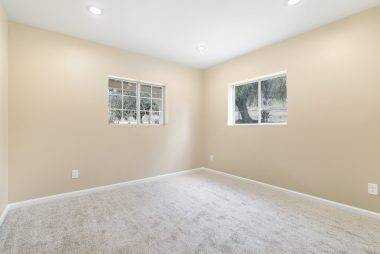 Front bedroom with new carpet, new paint, recessed lighting, double pane windows.