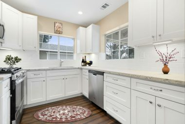 BRAND NEW KITCHEN with granite counter tops, subway tile back splash, soft-close shaker cabinets, under cabinet lighting, wood flooring, new sink, and double pane windows. This is a virtually staged photo.