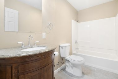 Private master bathroom with granite vanity, new flooring, and shower in tub.