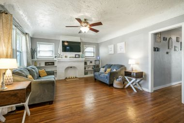 Original hardwood floors, custom bookshelves flanking the decorative fireplace, ceiling fan, and coved ceiling.