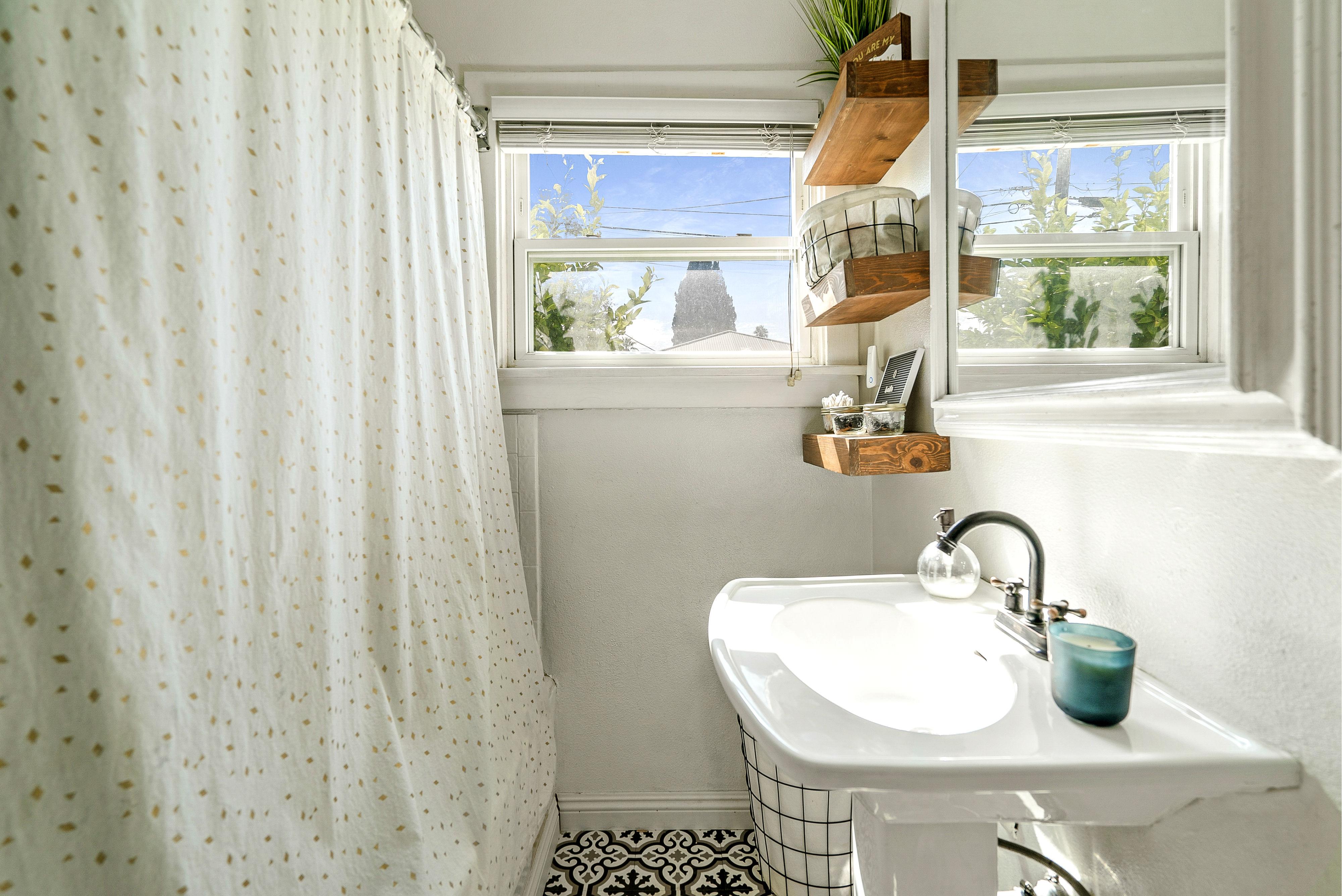 Bathroom with shower in tub, pedestal sink, floating shelves, and newer flooring.