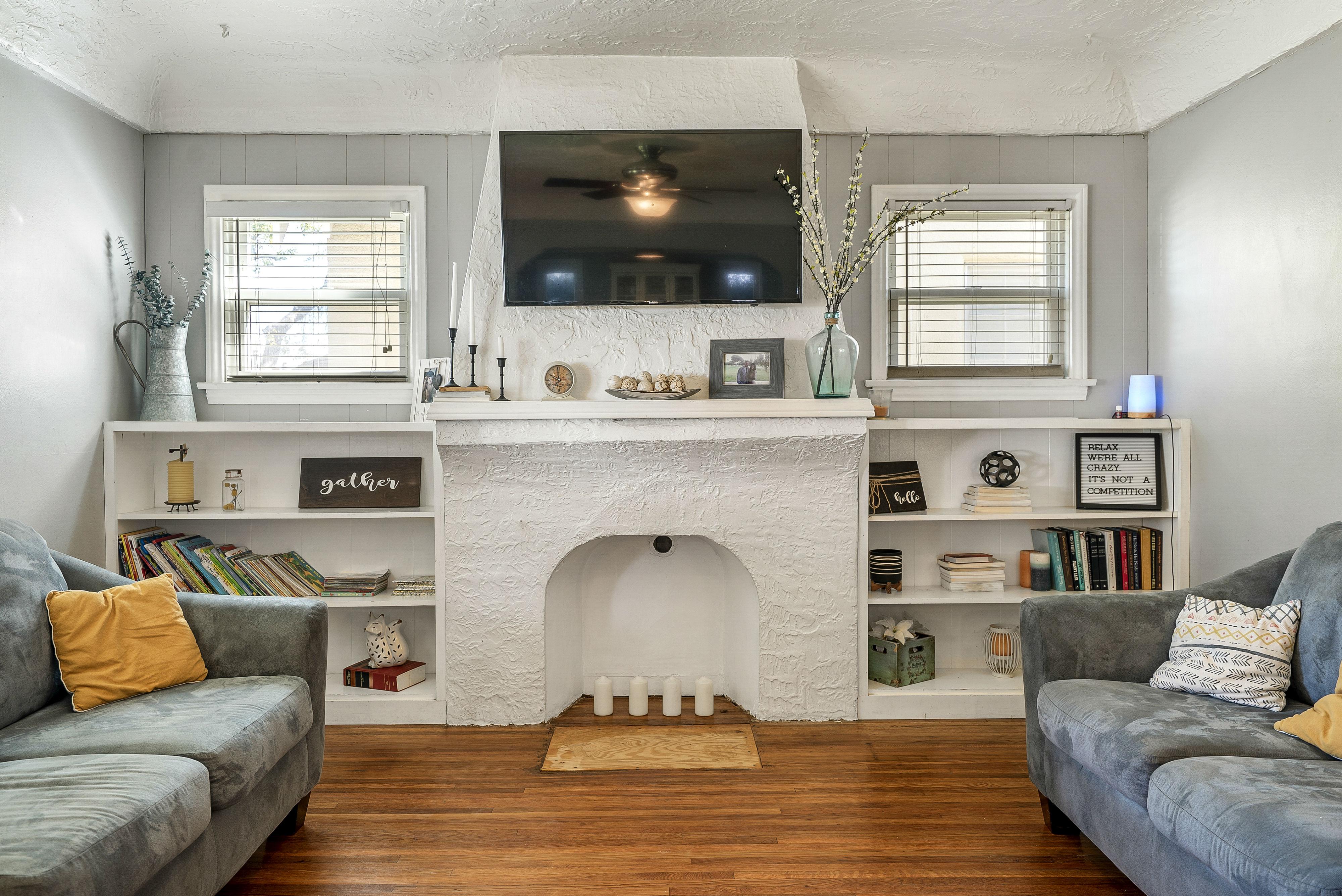 Custom bookshelves flanking decorative romantic fireplace.