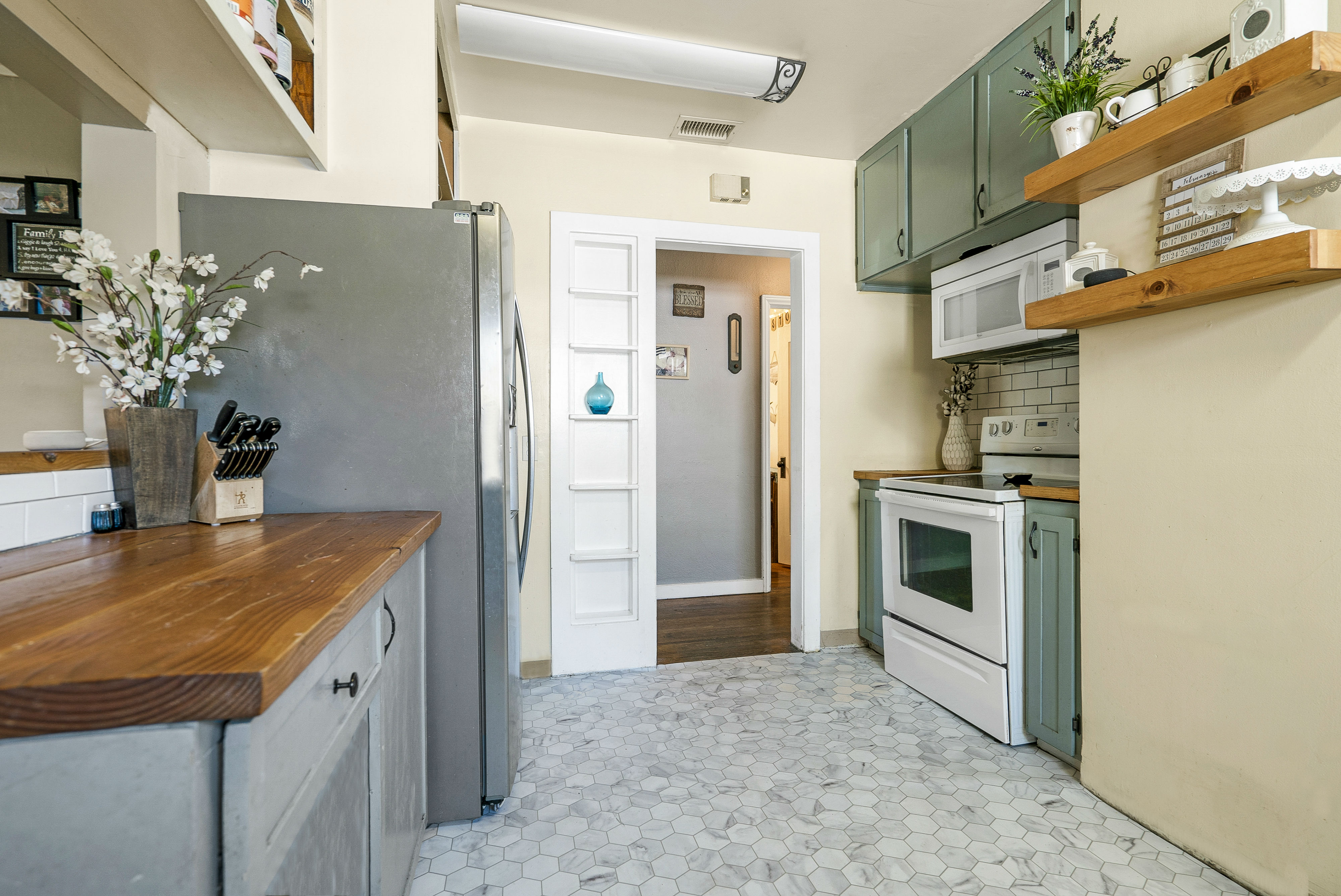Kitchen with new flooring, built-in microwave, and built-in vertical spice rack.