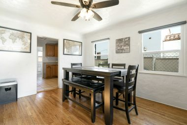 Spacious formal dining room with coved ceiling, ceiling fan, hardwood floors, and double pane windows. View into the remodeled kitchen.