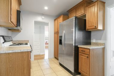 Remodeled kitchen with gas stove, built-in microwave, and tile flooring.