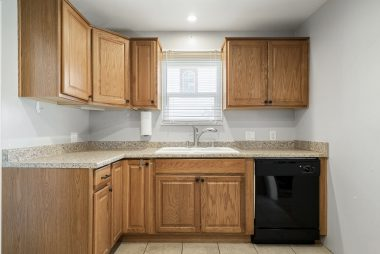 Remodeled kitchen with plenty of cabinetry, dishwasher, and tile flooring.