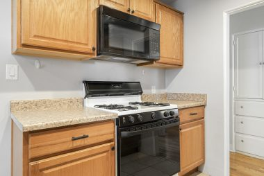 Gas stove and built-in microwave in remodeled kitchen.