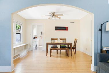 Formal dining room with ceiling fan, wood flooring, and built-in window seat and storage area.