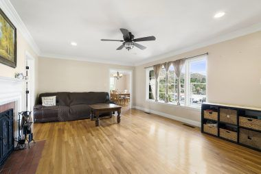 Living room with crown moulding, ceiling fan, beautiful original hardwood flooring, recessed lighting, and fireplace.