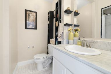 Private master bathroom with shower, stone counter top, and tile flooring.
