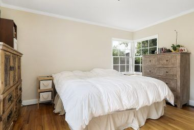 Master bedroom with lovely corner windows and original hardwood flooring and private bathroom.