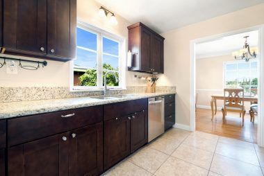 Remodeled kitchen with granite counters, built-in microwave, and tile floor.
