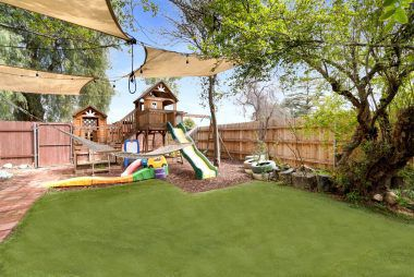 Side yard with artificial turf and play area for kids. Plenty of room to add a pool if desired.