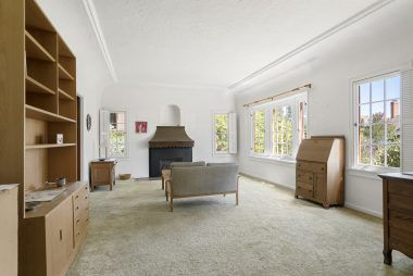 Spacious living room with fireplace and windows overlooking the professionally landscaped front yard.