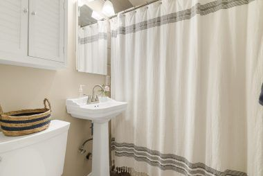 Bathroom with newer pedestal sink and toilet and flooring. Shower in tub.