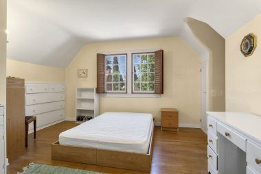 Bedroom #2 with cute little desk alcove and spacious built-in wardrobe drawers, as well as exposed hardwood flooring.