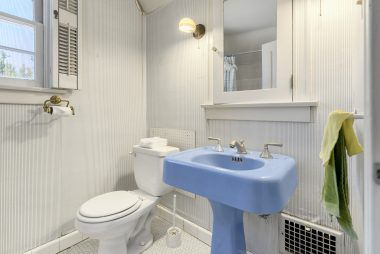 Master bathroom with shower in tub with original honeycomb tile flooring, as well as original cornflower blue pedestal sink and matching tub.
