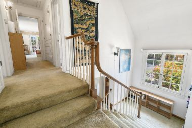 View from 2nd staircase landing with window overlooking the front yard, and view into hallway leading to the master bedroom suite.
