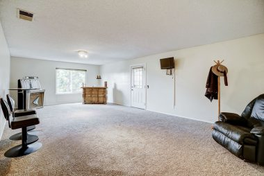 Huge downstairs bonus room with doorway leading to back patio with spa, and view of expansive backyard.