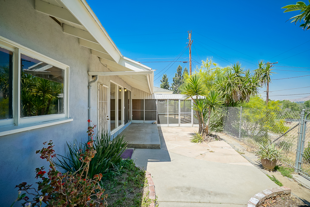 Low-maintenance paved portion of backyard with screened patio which is ideal for Al fresco dining or keeping your small pets safe from coyotes and hawks. The views are incredible from this back yard!