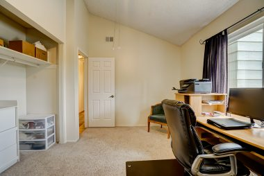 Third upstairs bedroom with cathedral ceiling, carpeting, and ceiling fan.