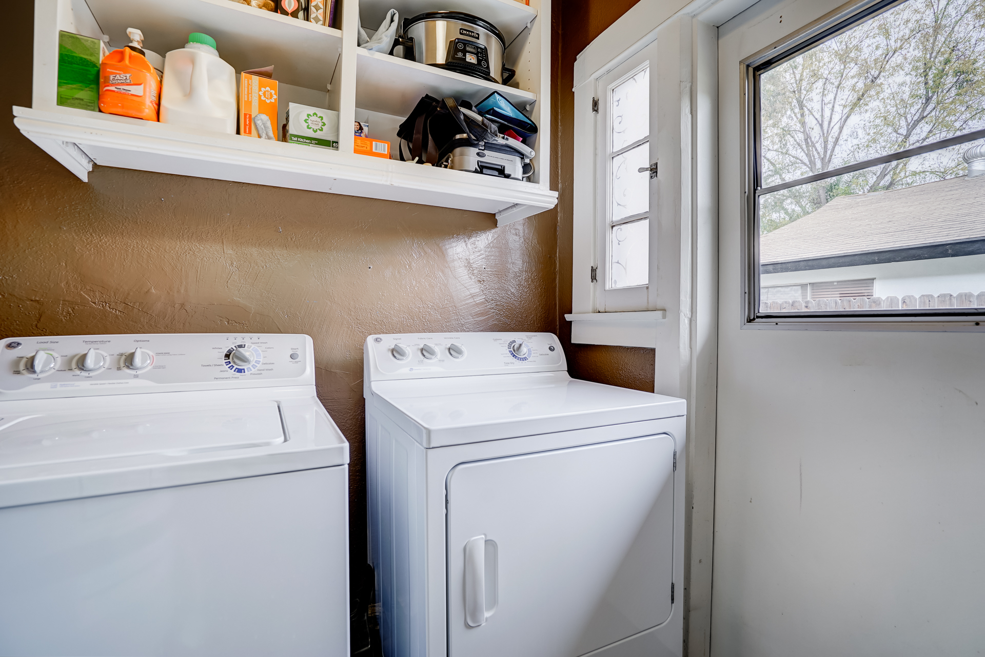 Separate laundry room with convenient shelving, newer water heater, and doorway to side yard.