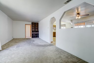 Alternate view of living room with built-in shelving and wall cut out into formal dining room and kitchen.