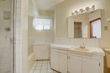 Bathroom with separate shower and tub, as well as tile floor and tile counters, with ample storage.