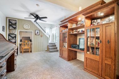 Family room with staircase leading to loft. Great use of under-staircase space with built-in shelving and desk cutout.