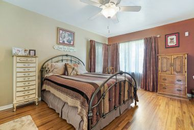 Front bedroom with hardwood floors and ceiling fan.