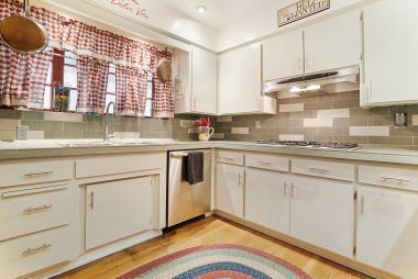 Updated kitchen with wood floors and stainless steel appliances.