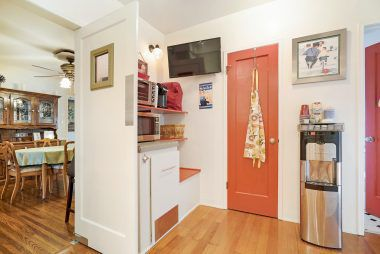 Doorway in kitchen leads to basement. Doorway partially photographed leads to charming half bath.