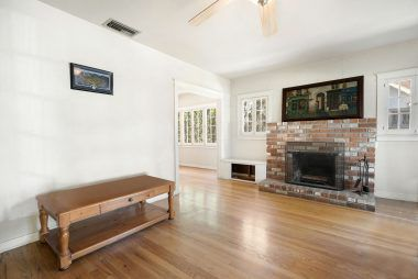 Living room with ceiling fan, and gas/wood-burning fireplace.