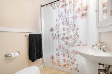 Tile floor, shower in tub, and pedestal sink.