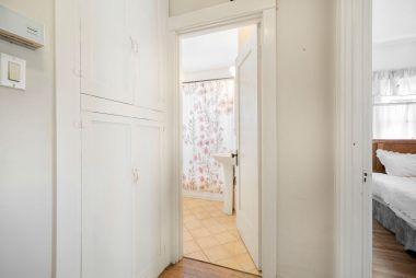 Hallway linen closet with doorway to bathroom and back bedroom.