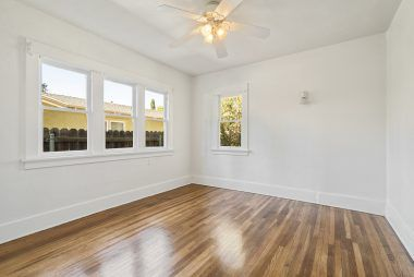 Back bedroom with ceiling fan and gleaming refinished hardwood floors.