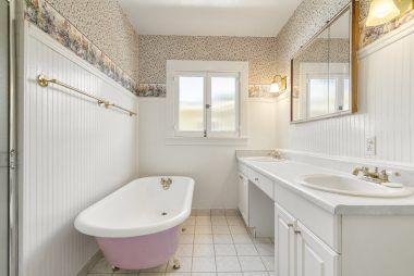 Separate shower, claw foot tub, dual vanity, bead board, and tile flooring in the bathroom.