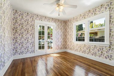 Front bedroom with ceiling fan and refinished hardwood floors.