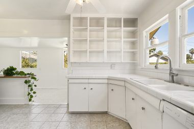 Tile floor, tile counters, dishwasher, open shelving, and updated plumbing in the light and bright kitchen, with opening into the laundry room.
