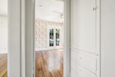 View from hallway and linen cabinet, into the front bedroom.