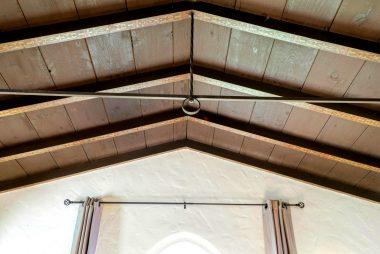 High-peaked ceiling with original exposed hand-painted wood beams.