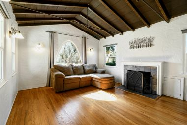 Lovely living room with hardwood floors, and high-peaked ceiling with original exposed hand-painted wood beams.