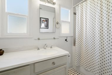 Lovely bathroom with large vanity, double pane windows, and shower in tub.