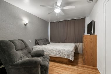Bedroom #2 with ceiling fan, hardwood floors, and double pane window.