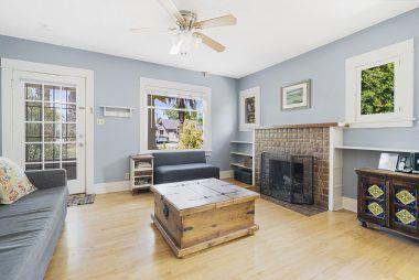 Hardwood floors, fireplace, ceiling fan, built-in shelving.