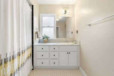 Hallway bathroom with stone counter top, tile flooring, and shower in tub.
