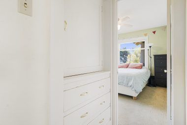 View of the linen cabinetry in hallway and into the front bedroom.